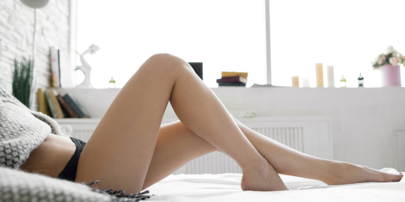 Perfect legs on bed with bent knees side view. Cropped image of erotically lying on bed beautiful woman in bedroom. Some free space